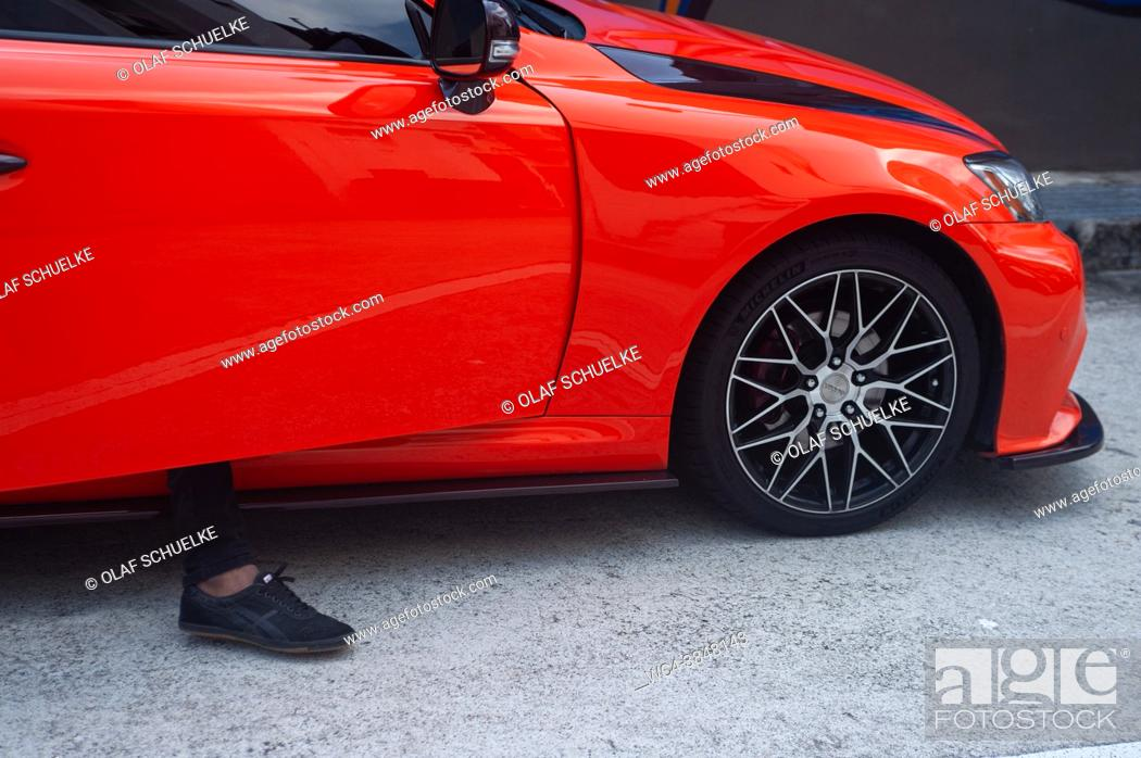 Stock Photo: Singapore, Republic of Singapore, Asia - A person gets out of a red sports car in the city district of Little India during the lasting corona crisis.