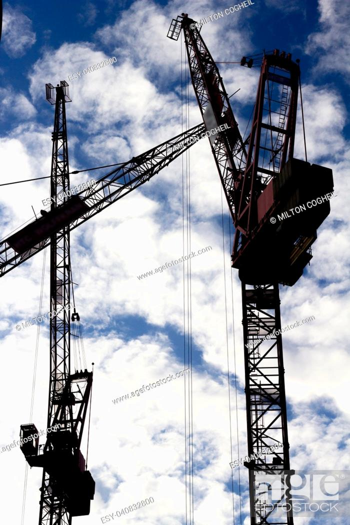 Stock Photo: Three tower cranes silhouetted against a cloud filled sky.