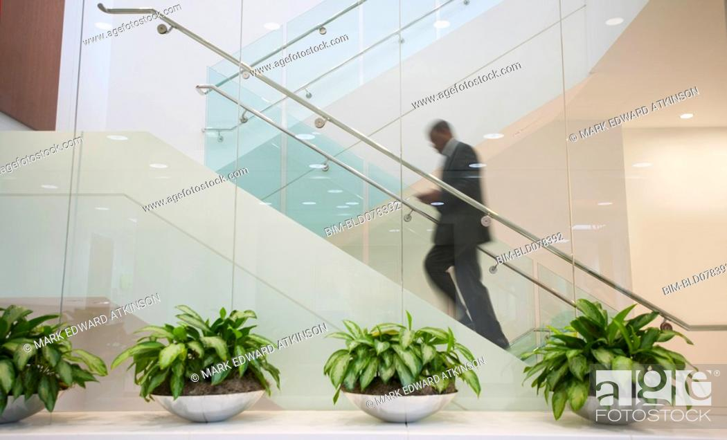 Stock Photo: African American businessman ascending staircase.