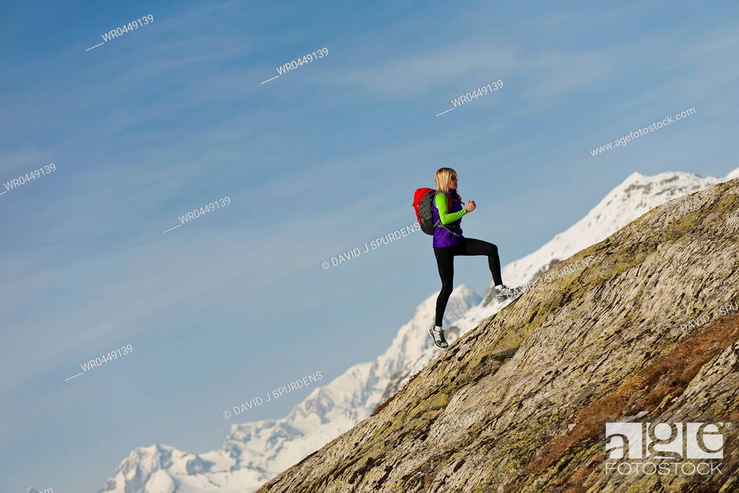 Stock Photo: A runner runs up a steep mountain rock face at high altitude.