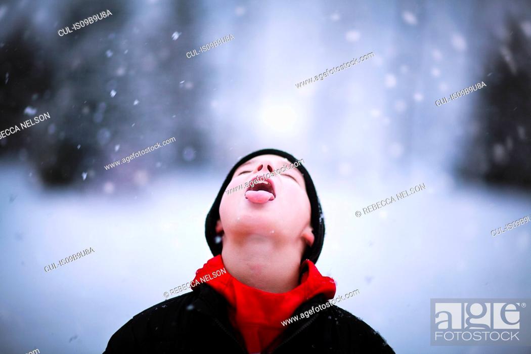 Photo de stock: Portrait of boy catching falling snow on tongue.