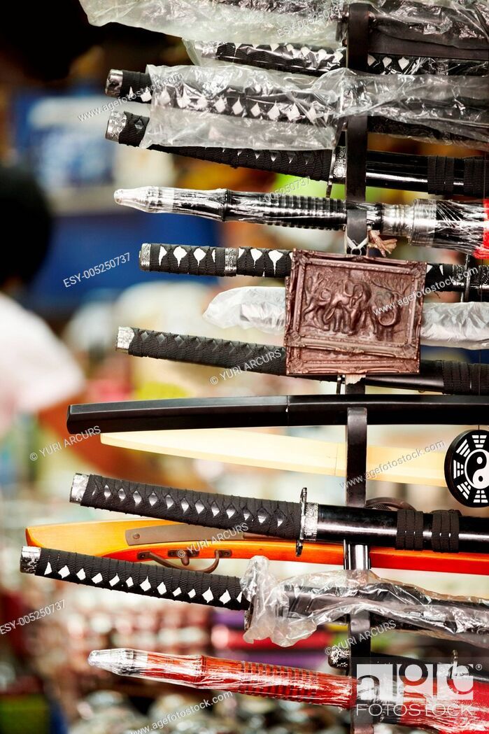 Stock Photo: View of numerous samurai swords on display at a market stall.