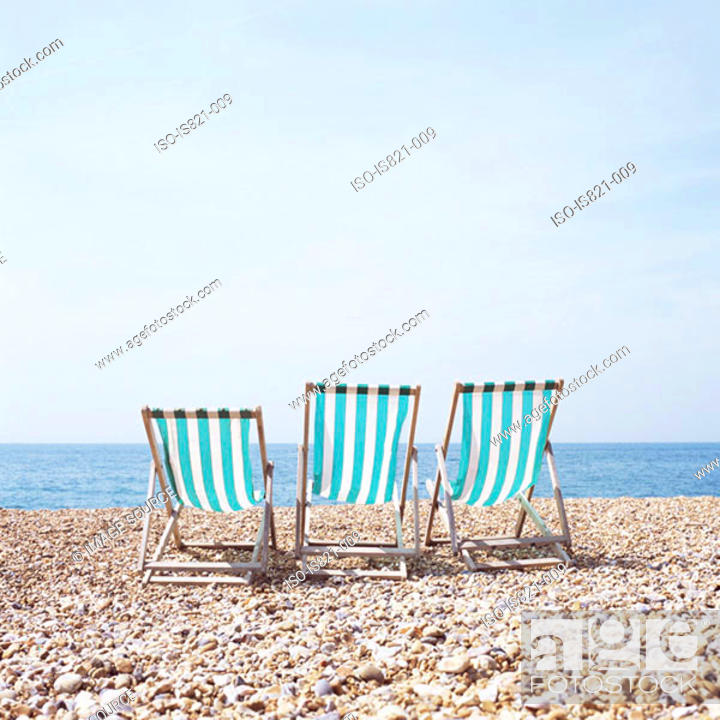 Stock Photo: Three deckchairs on a shingle beach.