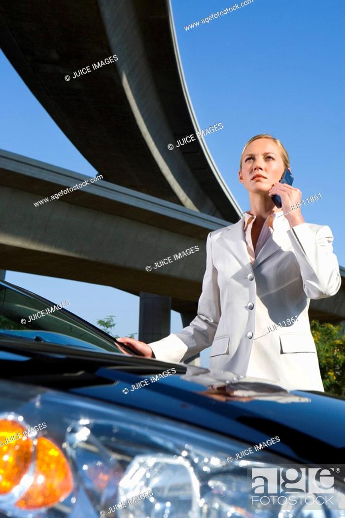 Stock Photo: Businessman using mobile phone by car beneath overpass, low angle view.