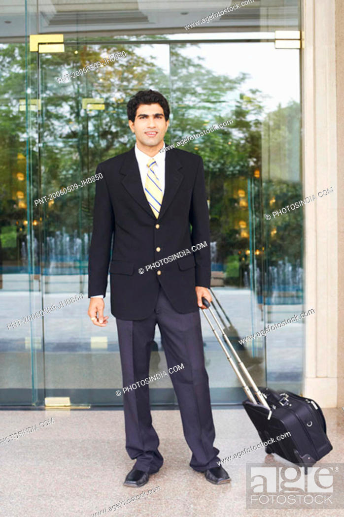 Stock Photo: Portrait of a businessman holding a suitcase.