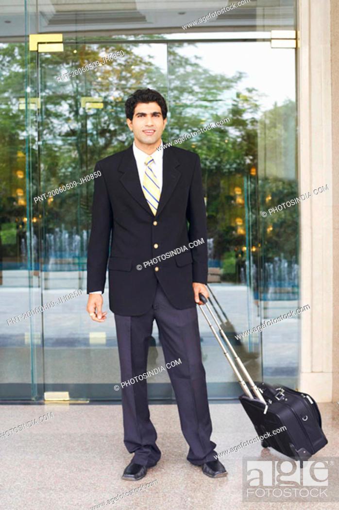 Stock Photo: Portrait of a businessman holding a suitcase.