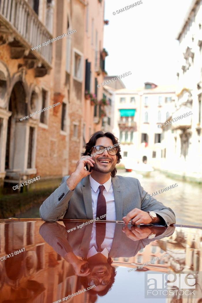 Stock Photo: Smiling businessman talking on cell phone and riding boat through canal in Venice.