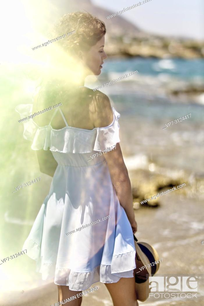 Stock Photo: woman on beach, sunlight, reflections, thoughtful, in Hersonissos, Crete, Greece.