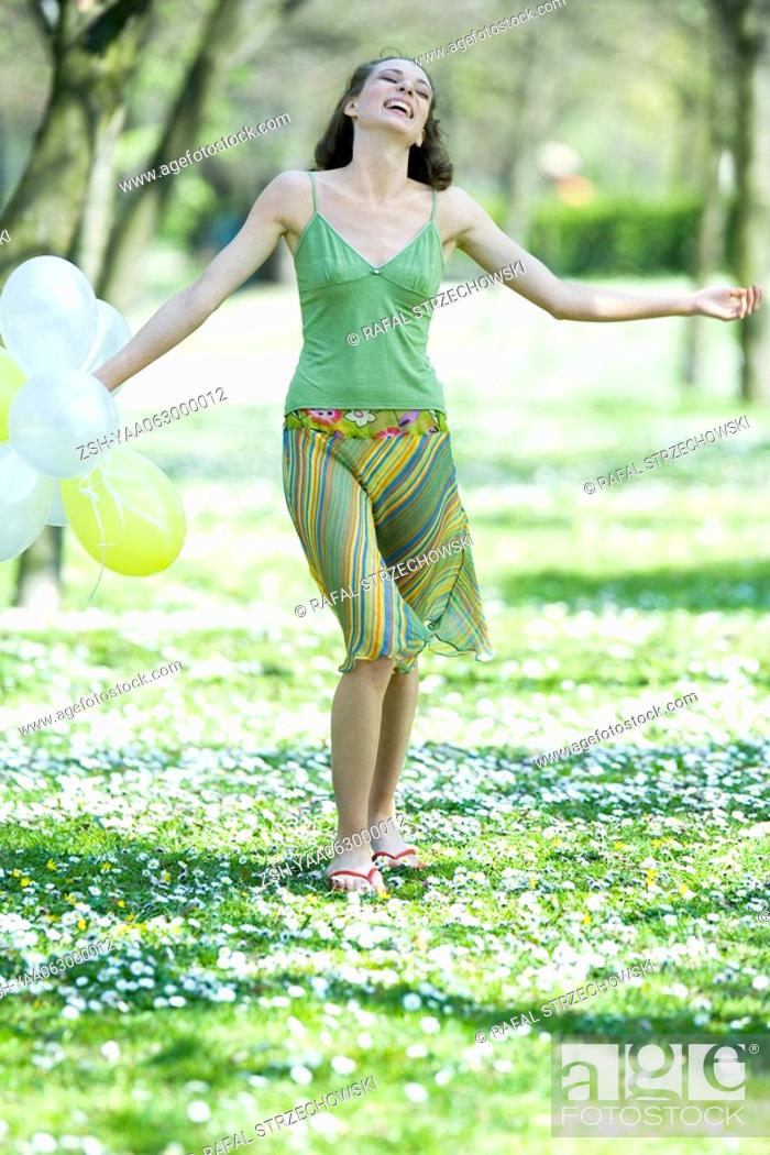 Stock Photo: Young woman walking in meadow, holding balloons, arms out, smiling.