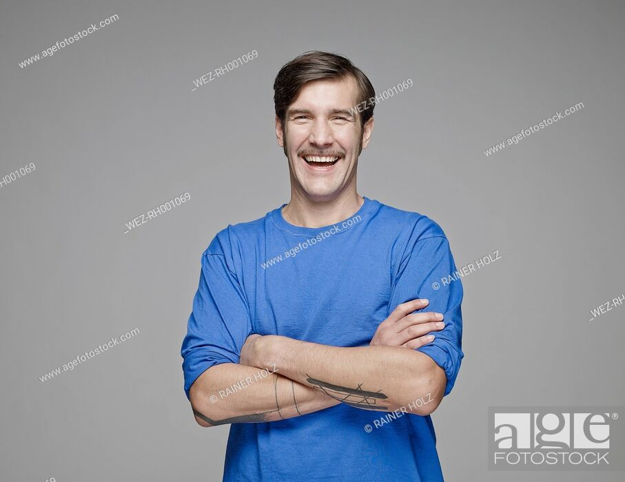 Stock Photo: Portrait of laughing man with crossed arms in front of grey background.