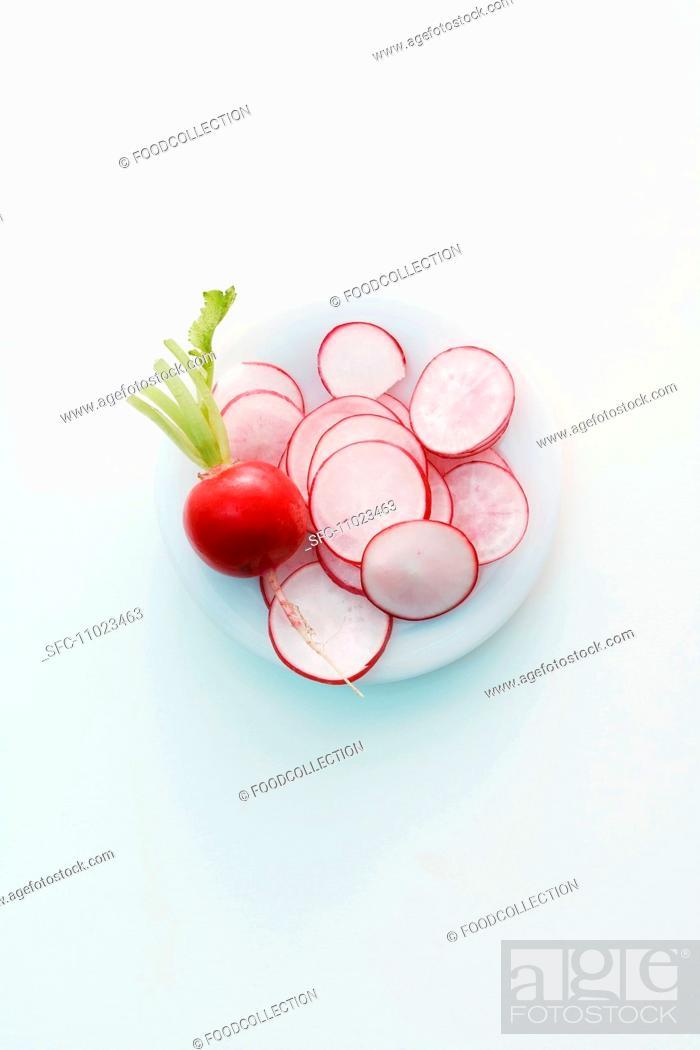 Stock Photo: A whole radish and sliced radishes.