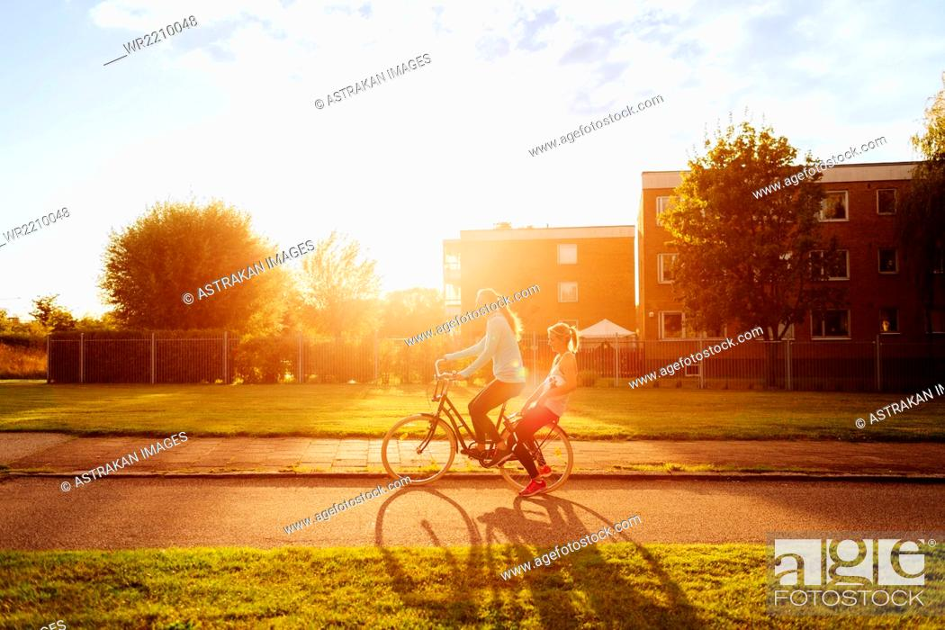Stock Photo: Side view of sporty women riding bicycle on street during sunset.