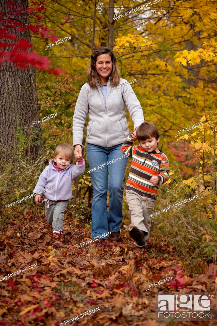 Stock Photo: Mother holding her children's hands ( girl and boy aged 1 and 3 respectively ) while walking up path through autumn leaves.