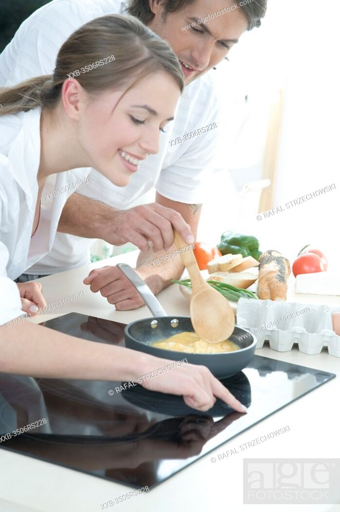 Stock Photo: couple making scrambled egg.