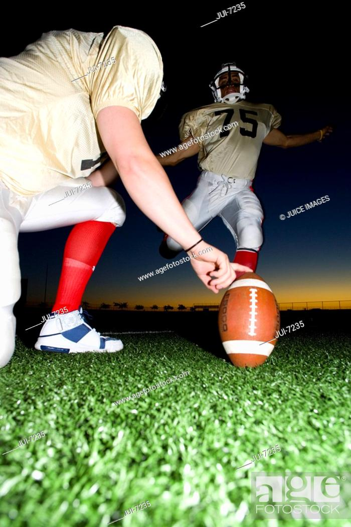 Stock Photo: American football player attempting to kick field goal, teammate holding ball vertically against pitch at sunset surface level.