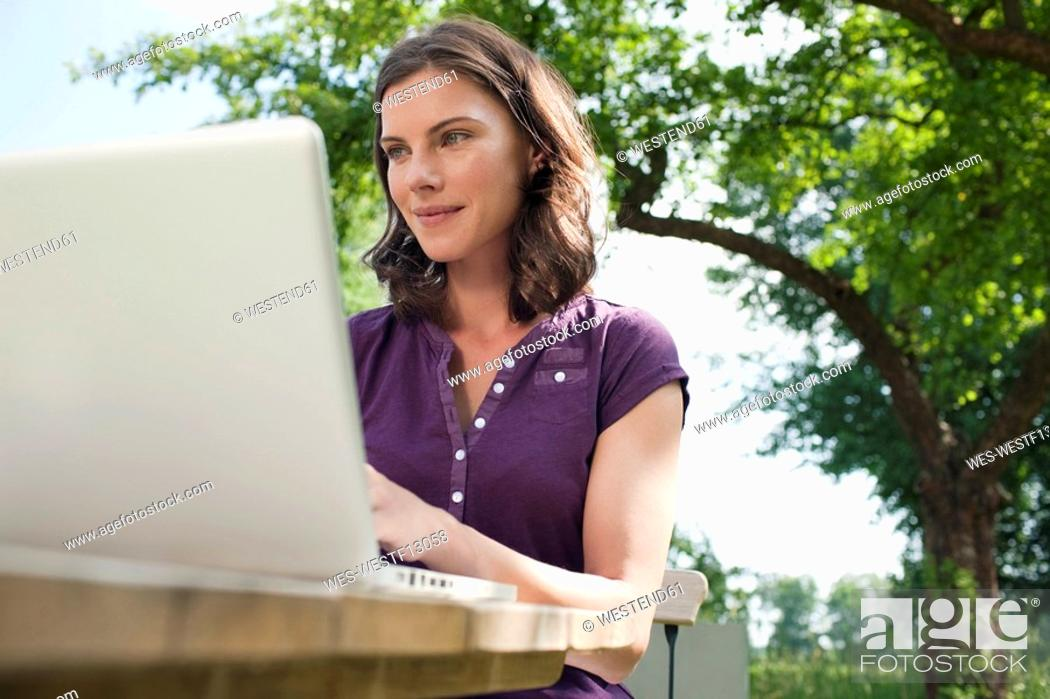 Stock Photo: Germany, Hamburg, Woman using laptop in garden.