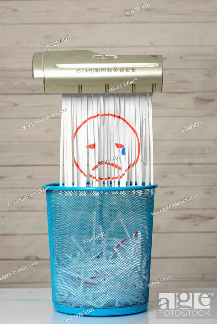 Stock Photo: Destroy the sadness. Shredder documents with printed images concept thrown in the trash. White background and blue basket.