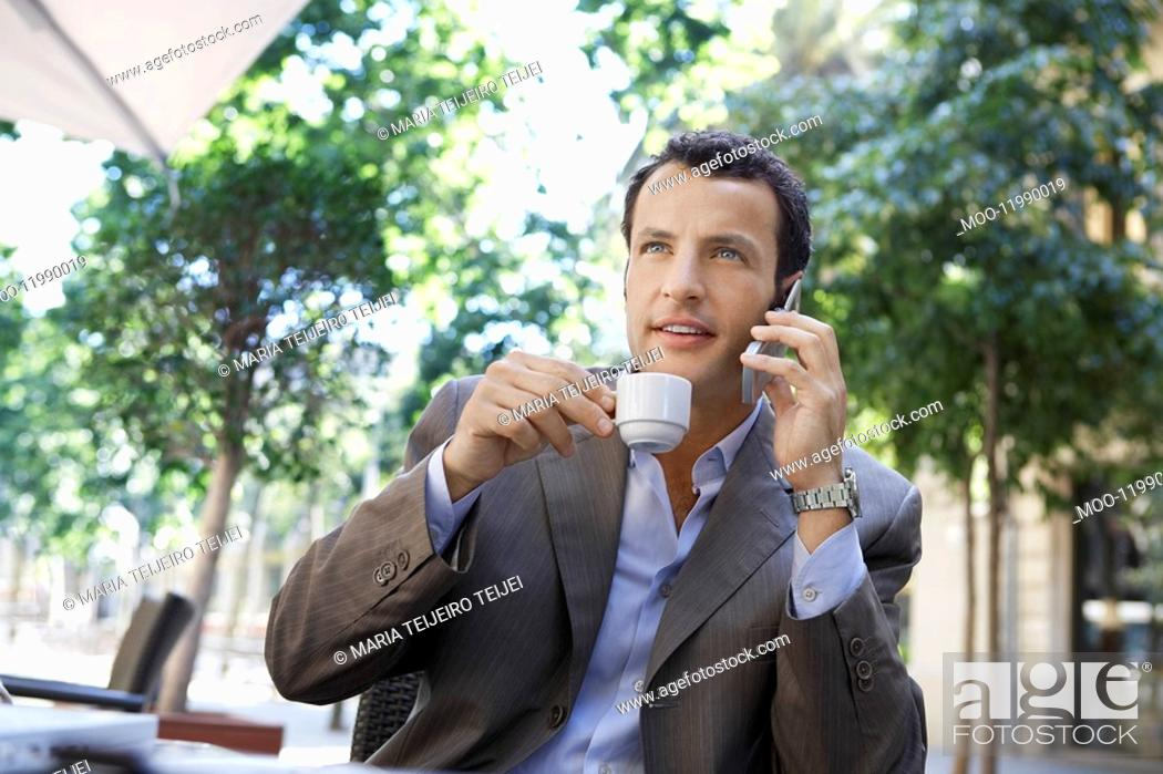 Stock Photo: Businessman using mobile phone at outdoor cafe.