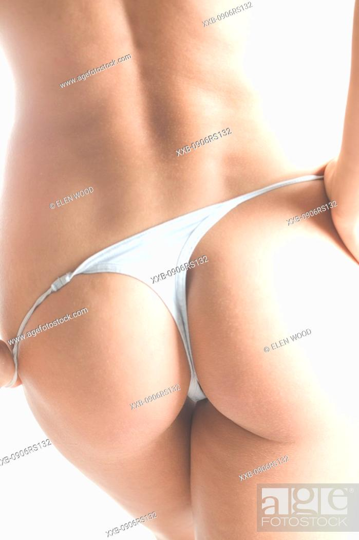 Stock Photo: woman takiing of g-string.