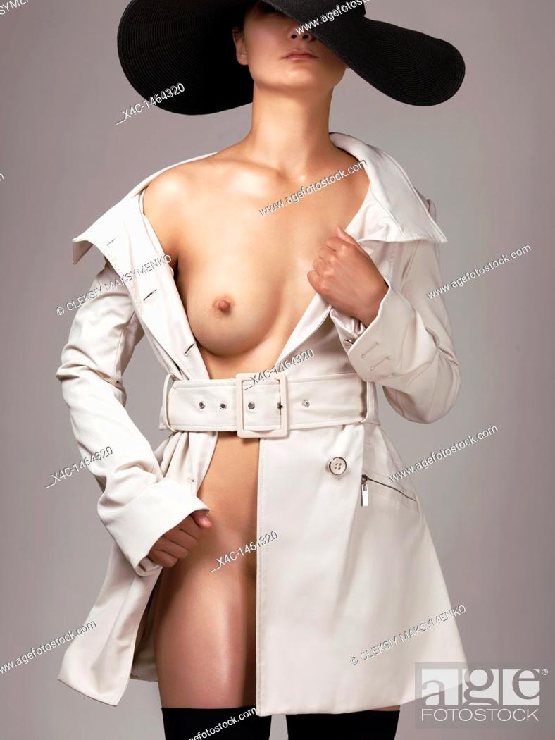 Stock Photo: Beautiful young half naked woman wearing a trench coat and a sun hat.