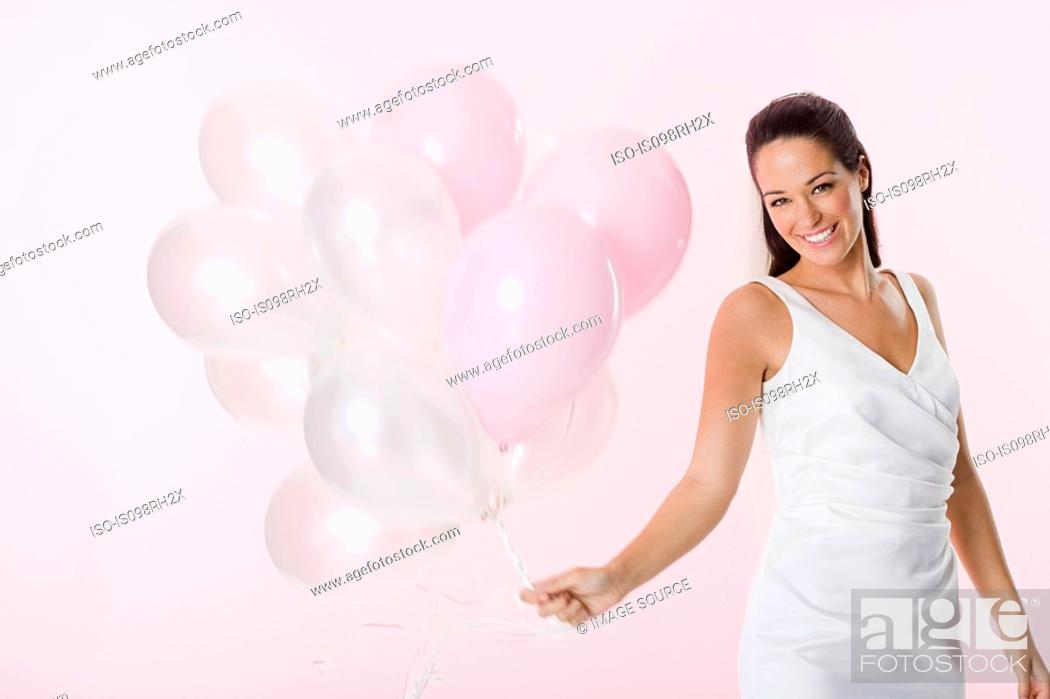 Stock Photo: Bride holding a bunch of balloons.