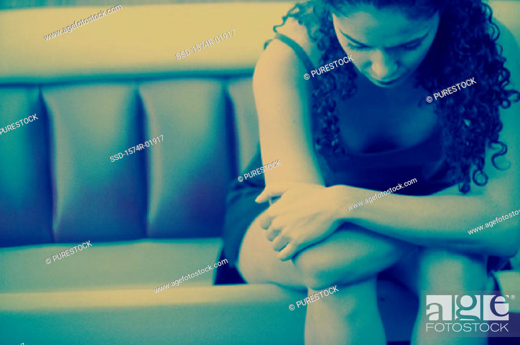 Stock Photo: Young woman sitting on a couch with her head down.
