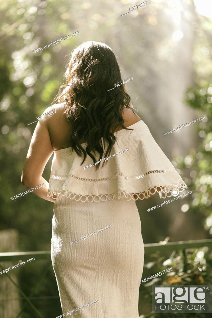 Stock Photo: Rear view of a woman in white dress standing outdoors.