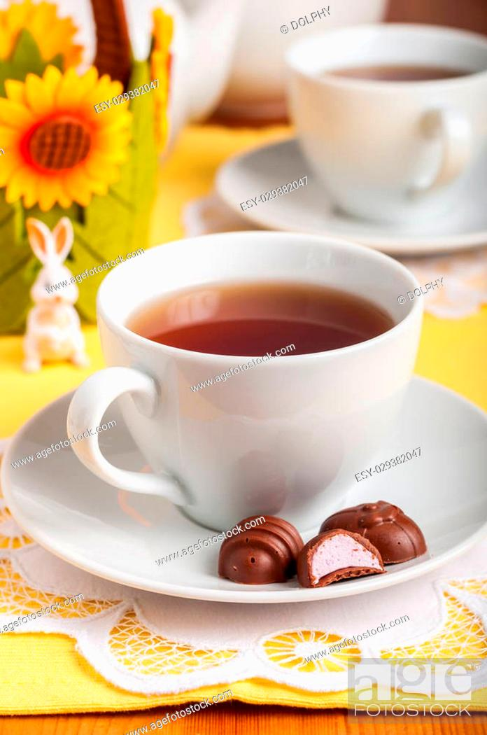 Stock Photo: A Cup of Tea and Easter Egg Shaped Chocolate Candies with Marshmallow Filling, copy space for your text.