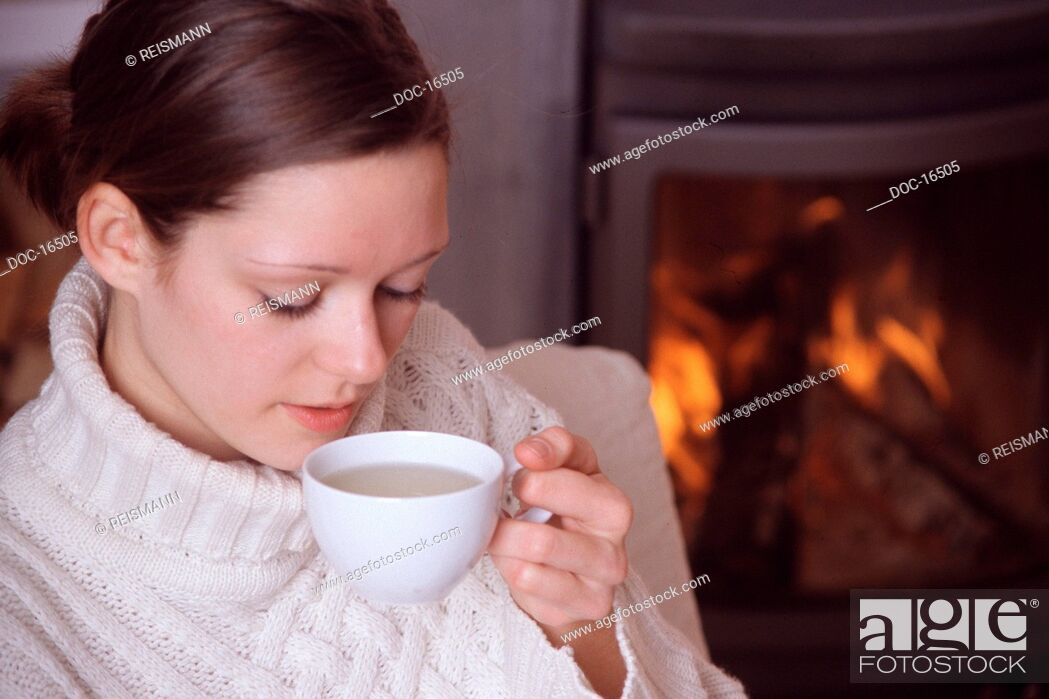 Imagen: woman sits in front of a chimney and drinks tea.