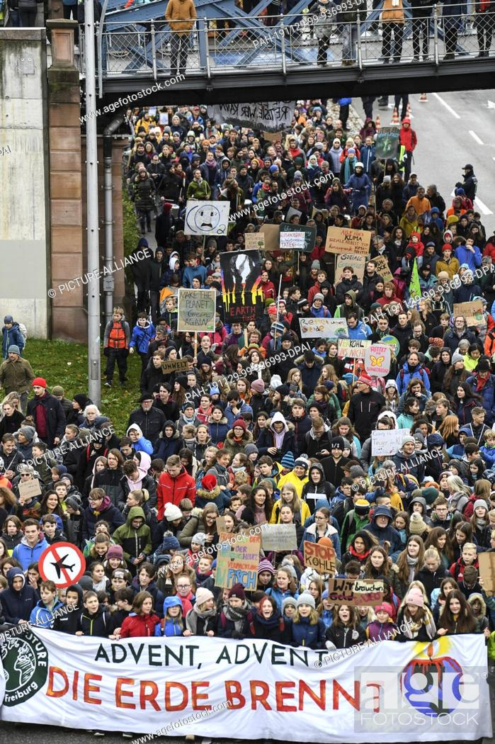 """Stock Photo: 29 November 2019, Baden-Wuerttemberg, Freiburg: At the action day of """"""""Fridays for Future"""""""" thousands of students walk through the city centre with the banner."""