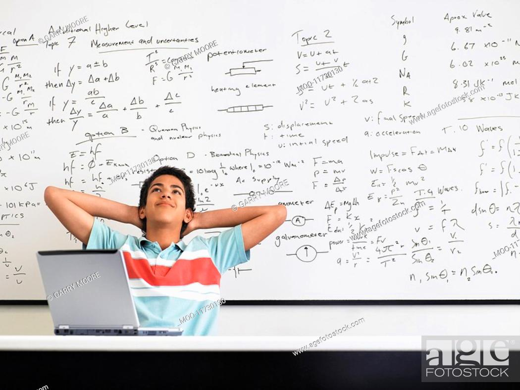 Stock Photo: Teenage boy sitting in front of whiteboard in classroom.