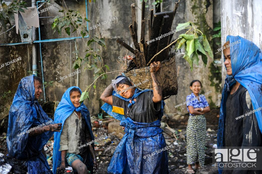 Stock Photo: Yangon, Myanmar, Asia - A group of sewer cleaners wearing simple protective clothing made of torn plastic bags cleans out the city's clogged open sewers.
