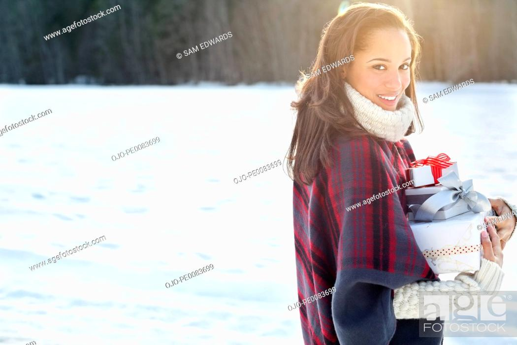 Stock Photo: Portrait of smiling woman carrying Christmas gifts in snow.