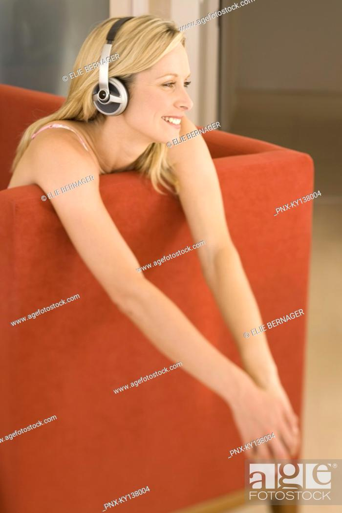 Stock Photo: Young woman listening to music with headphones.