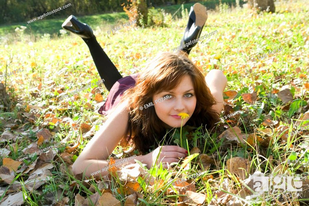 Stock Photo: Pretty young woman is lying on grass with a single yellow flower in hand.