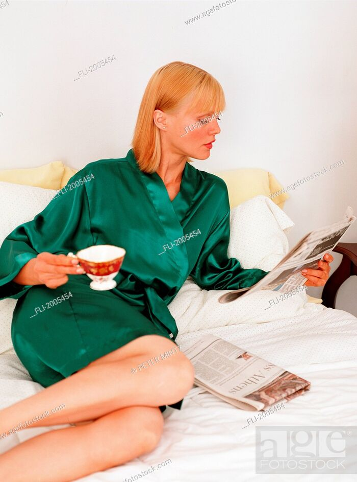 Stock Photo: Woman In Robe Reading Paper With Cup Of Tea On Bed.