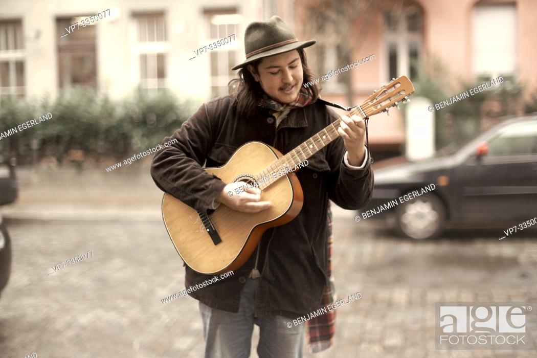 Stock Photo: man playing guitar at street in city.