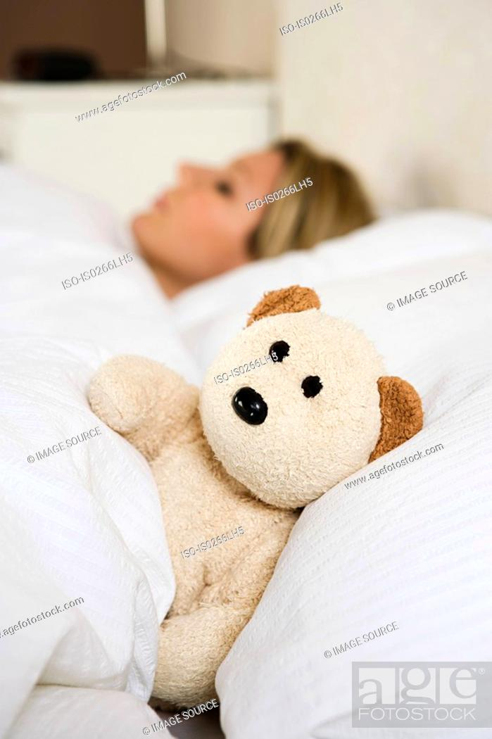 Stock Photo: Woman in bed with teddy bear.