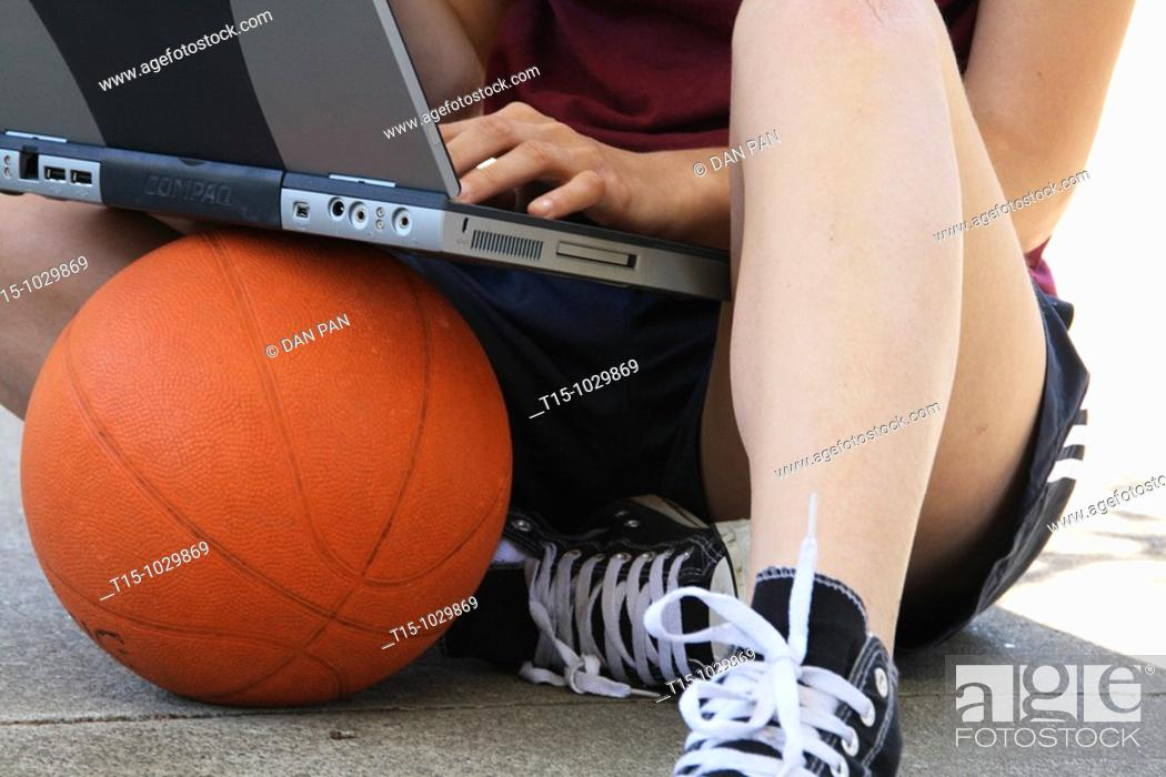 Stock Photo: woman using a laptop sitting on top of a basketball.