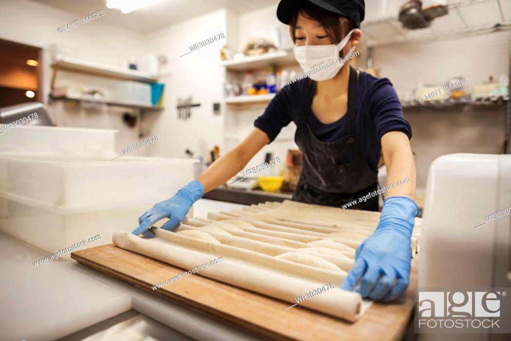 Stock Photo: Woman working in a bakery, wearing protective gloves and mask, placing dough on large wooden board.
