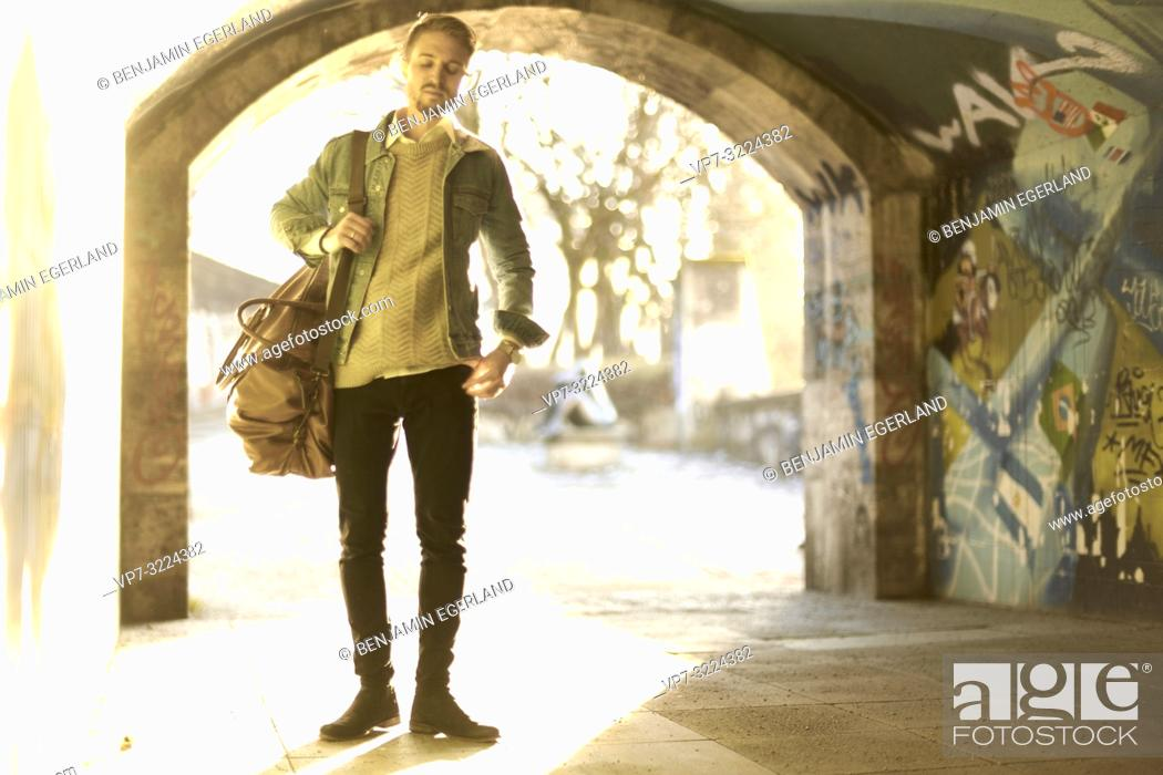Stock Photo: young man, fashionable, standing in underpass.