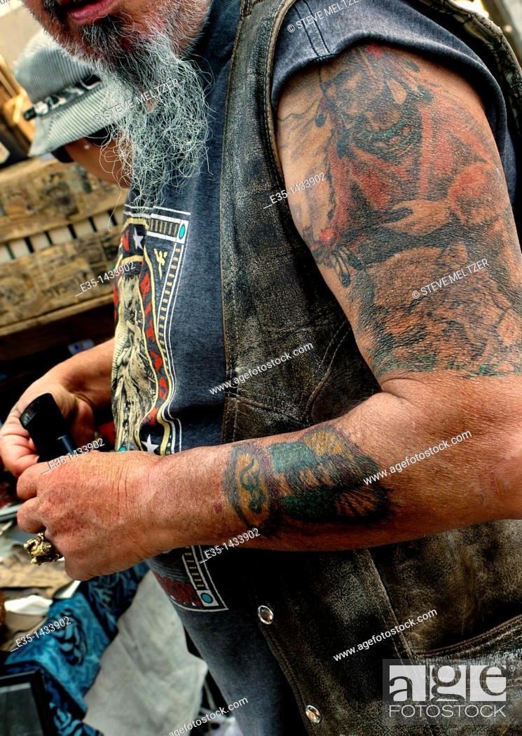 Stock Photo: An old motorcyclist rider's tattoos have not aged well.