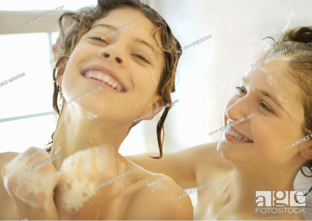 Stock Photo: Two preteen girls in shower, laughing.