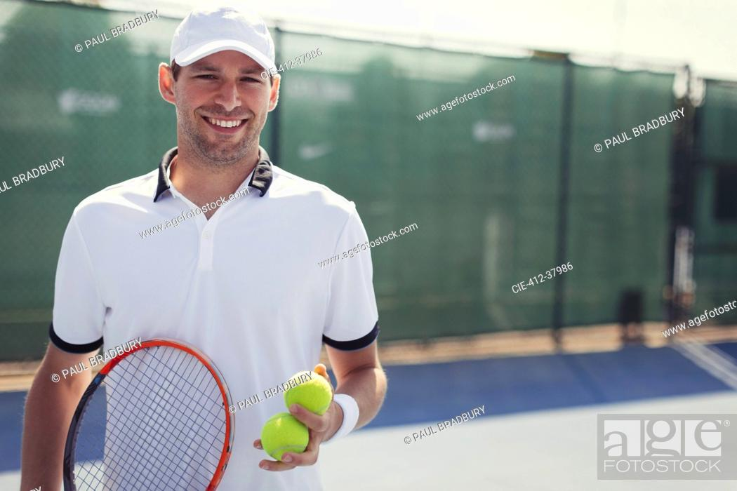 Stock Photo: Portrait confident, smiling young male tennis player holding tennis racket and tennis balls on sunny tennis court.