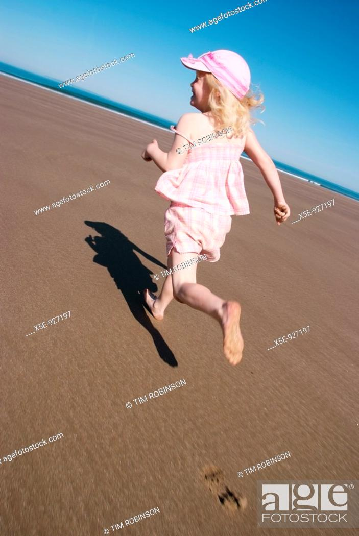 Stock Photo: Rearview 7 year blond girl running on beach, happy expression.