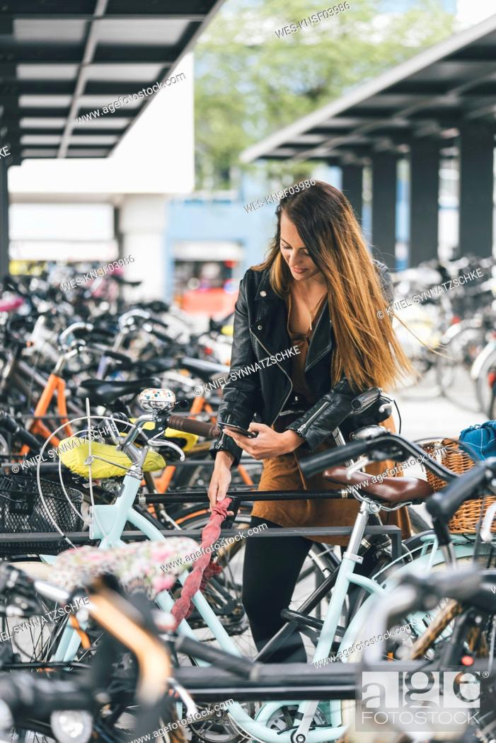 Photo de stock: Young woman with bicycle using cell phone in the city.