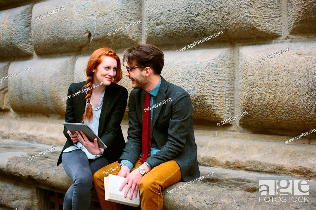 Stock Photo: Couple sitting using digital tablet, Florence, Italy.