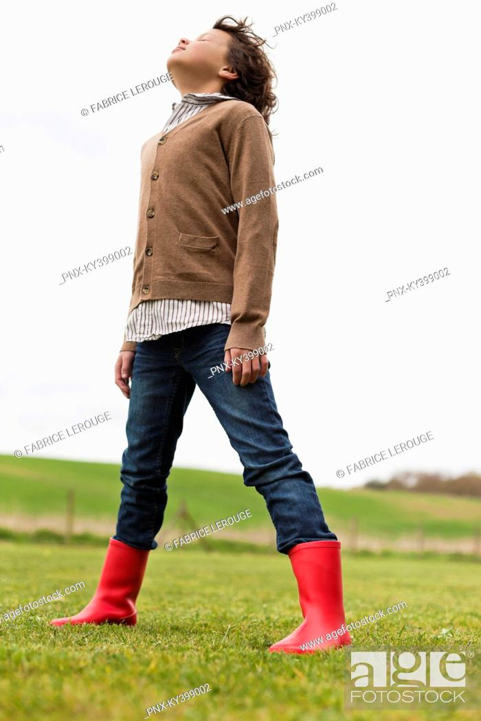 Stock Photo: Boy daydreaming in a field.