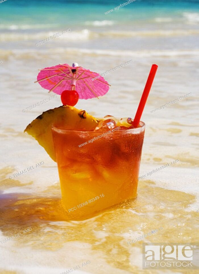 Stock Photo: A mai tai garnished with pinapple and a cherry, sitting in shallow water on the beach.
