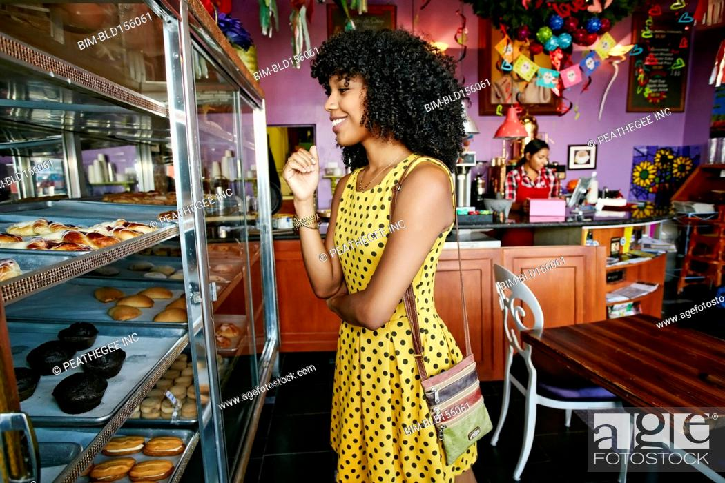 Stock Photo: Mixed race woman buying pastries in bakery.